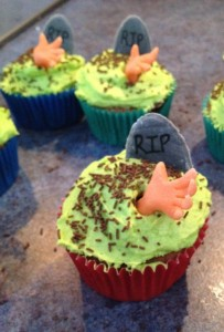 "...and graveyard cupcakes. The hands and tombstones are made from fondant. The ""dirt"" is chocolate sprinkles."