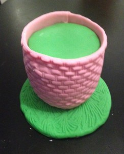 cut green fondant with a round cutter to sit on top. Then stamp a basket weave pattern onto fondant and cut strip wide enough to cover cake allowing for top to sit higher than cake edge. Position towards the back of a  covered cake board.