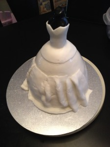 Once the cake hase been torted, iced and ganached, I covered it in a first layer of fondant. Then inserted the torso and began the dress design.