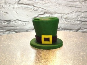 Cut a smaller diameter circle from the green fondant that is the right size for the top of the hat and attach to seal in the chocolates.